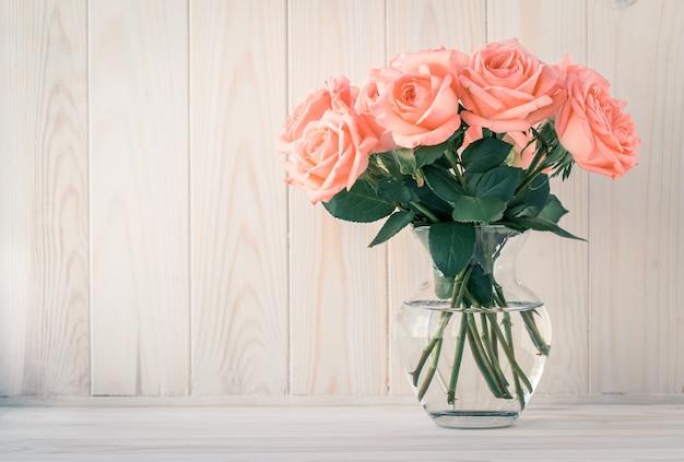 Ramo de rosas en un jarrón sobre una mesa de madera clara.
