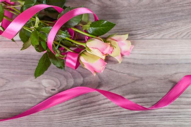 Ramo de rosas con lazo rosa sobre madera