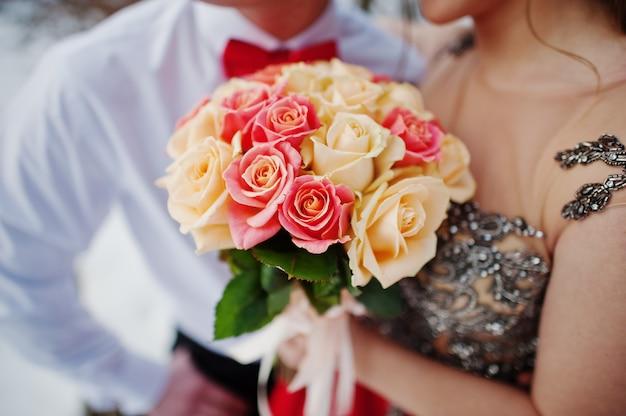 Ramo de rosas en manos de la pareja.