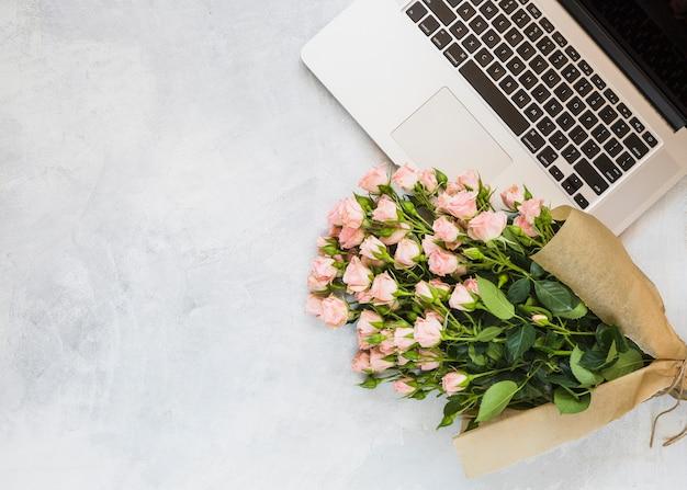Ramo de rosas con un portátil abierto sobre fondo de hormigón.