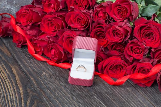 Un ramo de rosas rojas y un anillo de compromiso dorado