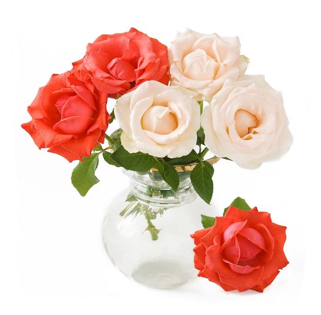 Ramo de rosas rojas y blancas en un jarrón sobre blanco, primer plano