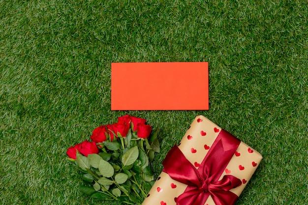 Ramo de rosas rojas y caja de regalo con sobre sobre hierba verde.