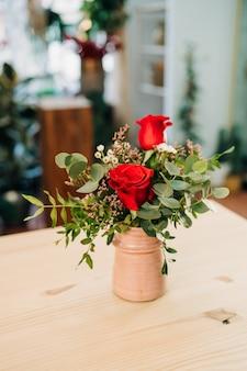 Ramo de rosas rojas en un jarrón rosa sobre una mesa de madera