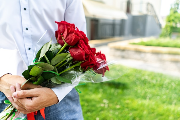 Un ramo de rosas rojas en manos de un hombre de cerca.