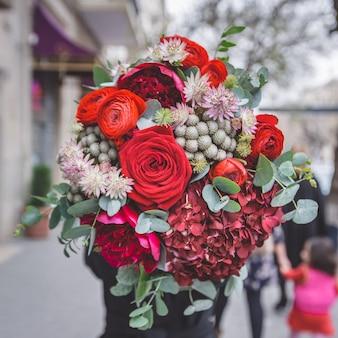 Un ramo de rosas rojas, peonías y flores decorativas verdes con hojas.