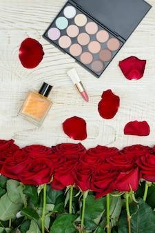 Ramo de rosas rojas, perfume, lápiz labial y paleta de sombras de ojos w