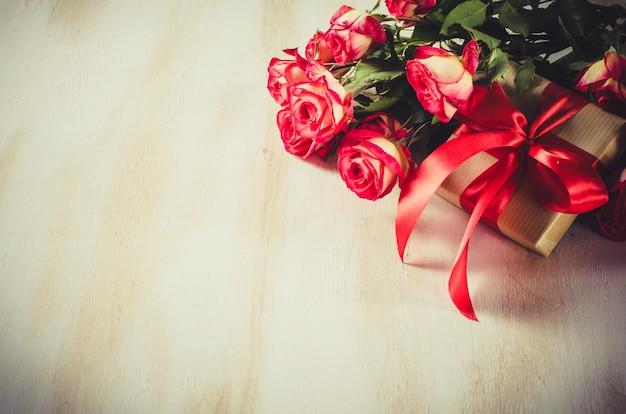 Ramo de rosas rojas y presente en mesa de madera.