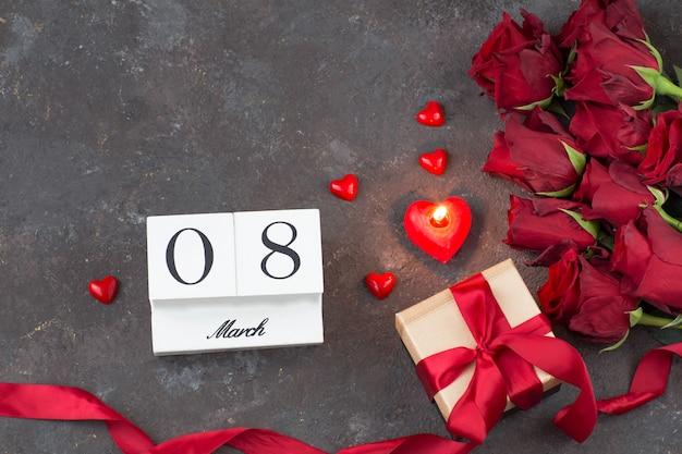 Un ramo de rosas rojas, un regalo en una caja, velas en forma de corazón y la fecha del 8 de marzo