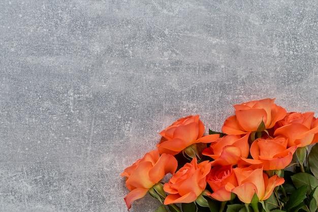 Ramo de rosas rojas sobre fondo de hormigón gris.