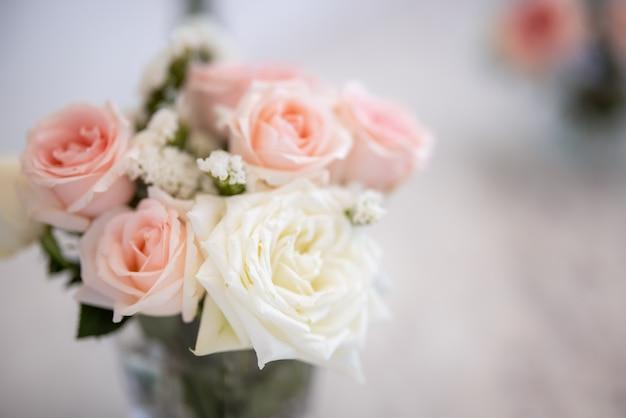 Ramo de rosas rosadas borrosas en florero pastel