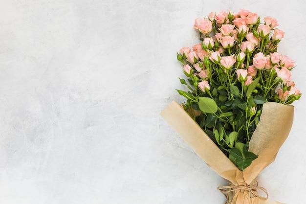Ramo de rosas rosadas envuelto en papel marrón sobre fondo de hormigón.