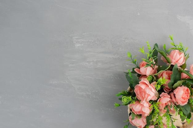 Ramo de rosas rosadas con hojas sobre superficie gris