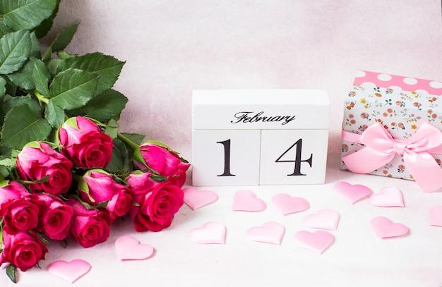 Ramo de rosas rosadas, un regalo en una caja, corazones de satén y la fecha del 14 de febrero en cubos
