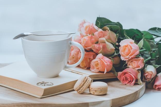 Ramo de rosas rosadas sobre una tabla de madera con un vaso encima del libro y galletas de macarrón