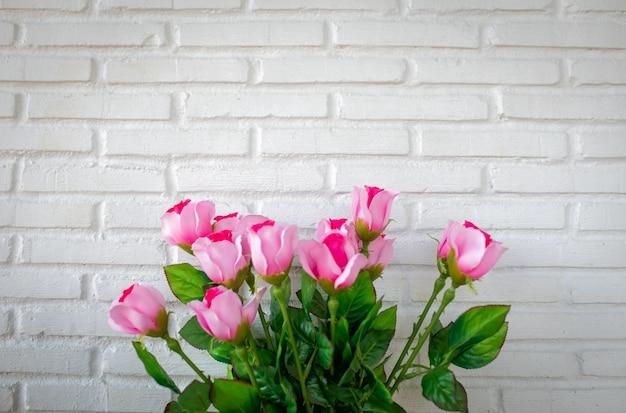 Ramo de rosas sobre fondo de pared de ladrillo blanco con espacio de copia.