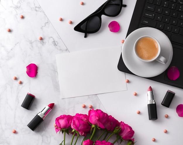 Ramo de rosas, taza de café, portátil, gafas de sol y lápiz labial en la mesa blanca.