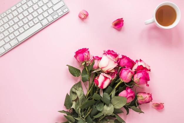 Ramo de rosas con taza de té y teclado.