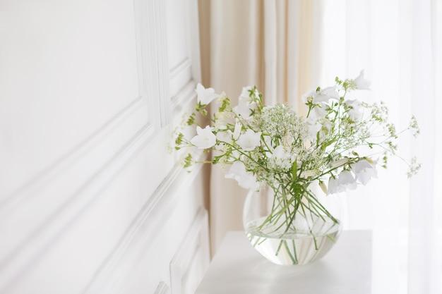 Ramo de suaves campanas en florero. luz de la mañana en la habitación. decoración para el hogar suave, florero de vidrio con flores blancas