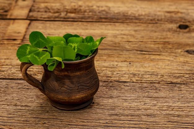 Ramo de trébol fresco en taza de cerámica. símbolo de buena suerte, concepto del día de san patricio
