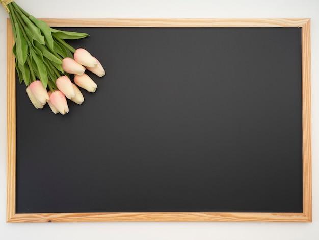 Ramo de tulipán colocado en el marco de la pizarra.