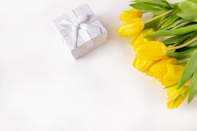 Ramo de tulipanes amarillos y cajas de regalo sobre un fondo blanco con lugar para agregar notas.