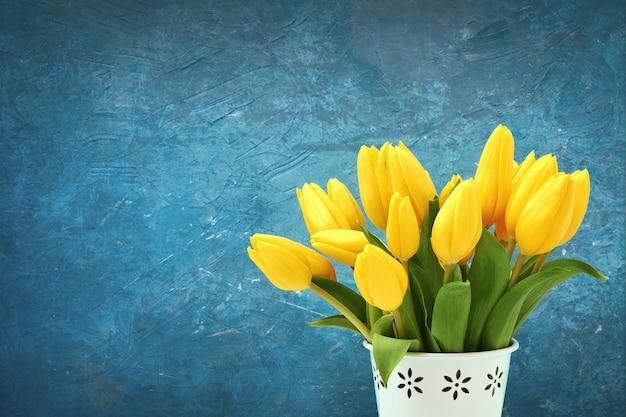 Ramo de tulipanes amarillos en florero blanco.