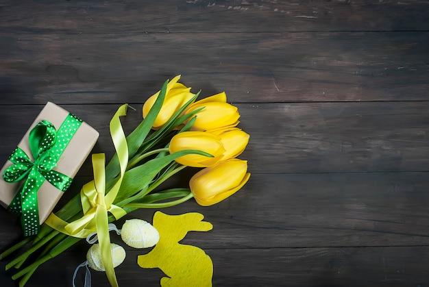 Ramo de tulipanes amarillos y huevos de pascua chikken con una cinta azul sobre un fondo de madera