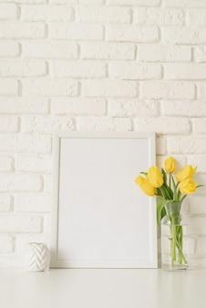 Ramo de tulipanes amarillos en un jarrón de vidrio y marco de fotos en blanco sobre un fondo de pared de ladrillo blanco. diseño de maqueta