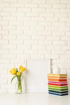 Ramo de tulipanes amarillos en un jarrón de vidrio, pila de libros coloridos y marco de fotos en blanco sobre un fondo de pared de ladrillo blanco. diseño de maqueta