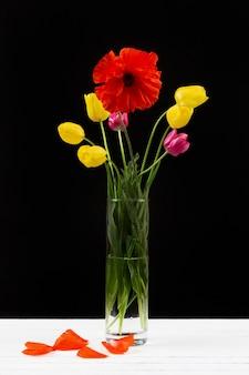 Ramo de tulipanes amarillos y morados y amapola roja en un jarrón de vidrio sobre fondo negro