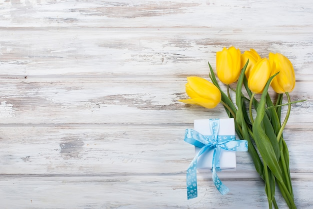 Ramo de tulipanes amarillos y un regalo con una cinta azul en un fondo de madera