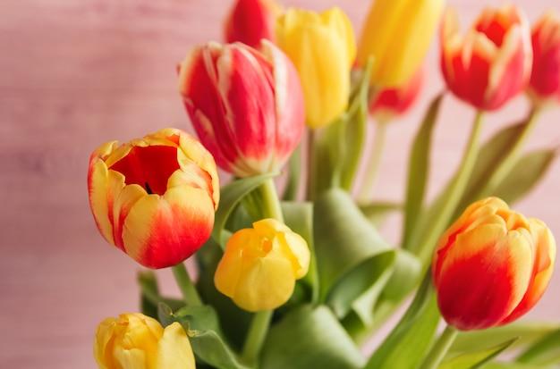 El ramo de tulipanes amarillos, rojos y rosados en un fondo de madera rosado copia el espacio.