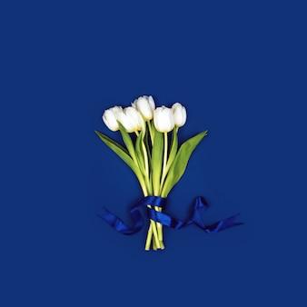 Un ramo de tulipanes blancos atados con una cinta.