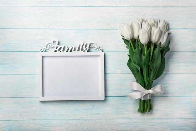 Un ramo de tulipanes blancos con un marco para la inscripción en tableros azules