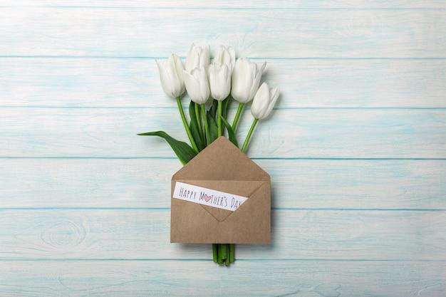 Un ramo de tulipanes blancos con la nota y el sobre del amor en los tableros de madera azules. día de la madre