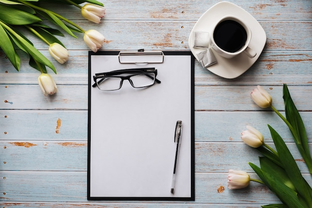 Ramo de tulipanes blancos con un portapapeles vacío y una taza de café en una mesa de madera