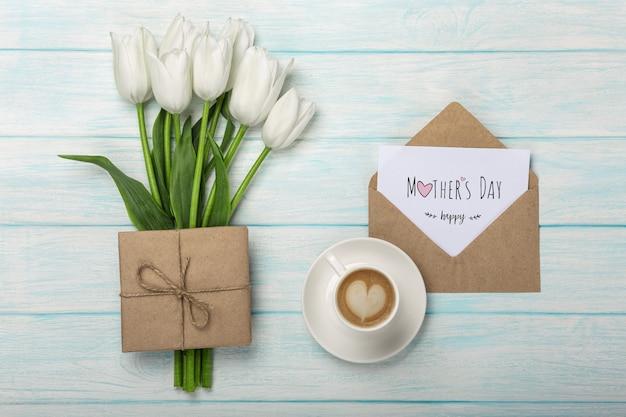 Un ramo de tulipanes blancos, una taza de café con una nota de amor y un sobre de tablas de madera azules. día de la madre