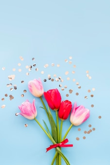 Ramo de tulipanes brillantes y confeti brillante.