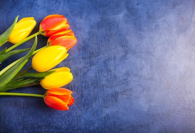 Ramo de tulipanes brillantes en mesa azul