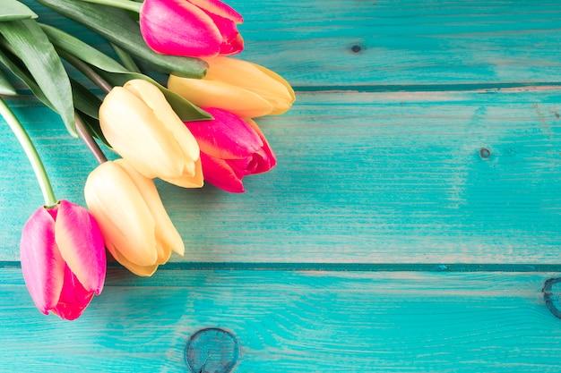 Ramo de tulipanes brillantes en mesa de madera