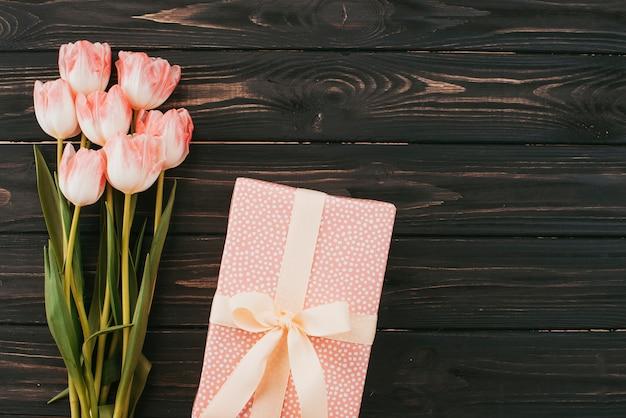 Ramo de tulipanes con caja de regalo en mesa de madera.