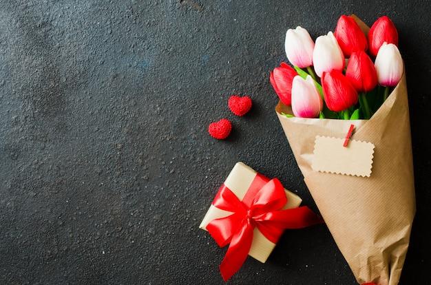 Ramo de tulipanes y caja de regalo sobre fondo oscuro.