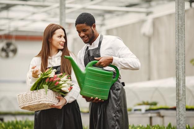 Ramo de tulipanes en un chico. chico y chica en invernadero. g. jardineros en delantales.