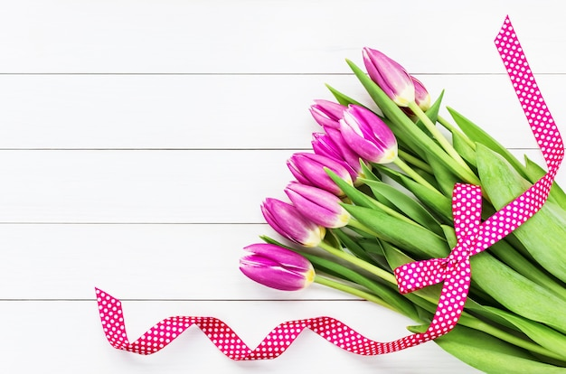 Ramo de tulipanes de color rosa brillante decorado con cinta rosa sobre fondo blanco de madera