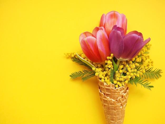 Ramo de tulipanes y flores de mimosa sobre fondo amarillo