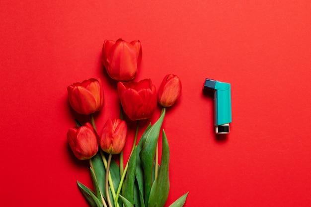 Un ramo de tulipanes flores y spray botella inhalador.