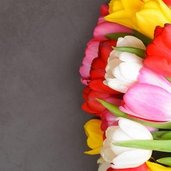Un ramo de tulipanes frescos, brillantes y multicolores sobre una superficie gris