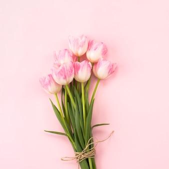 Ramo de tulipanes grandes en mesa rosa