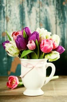 Ramo de tulipanes hermosos en mesa de madera